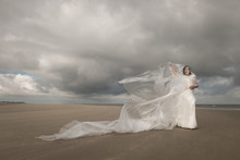Girl In White Dress Wrapped In Plastic Sheet Dancing On Beach Under Cloudy Sky