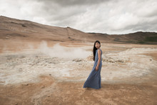 Girl In Blue Dress Standing On Geothermal Field In Iceland