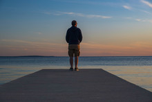 Man Standing On Dock And Watch...