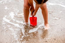 Child Plays On The Beach In The Sand With A Red Paddle. Children's Hands In The Sand On The Beach Close-up. A Child Builds A Sand Castle. On The Seashore. On The Ocean. Dirty Sand By The Sea