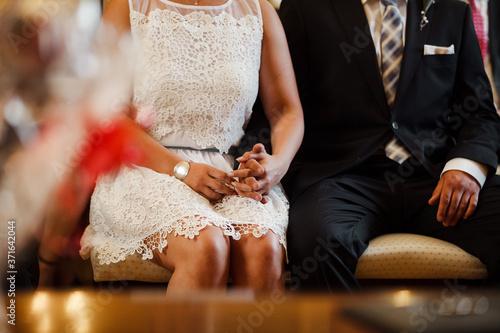 Photo Ein junges Ehepaar sitzt aufgeregt auf dem Standesamt