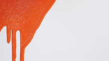 Bright Orange Paint Flows Down From White Canvas, Abstract Background, Art Minimalism, Painting Background With Colored Pigment On Textured Paper