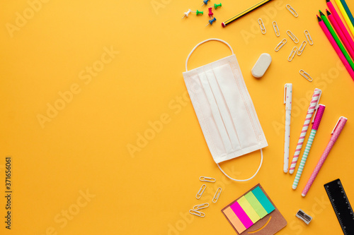 Photo Stock photo of back to school concept in the new normal with a face mask, some s