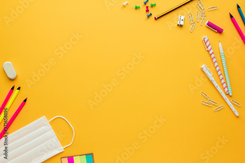 Fototapeta Stock photo of back to school in the new normal with a face mask, some stationer
