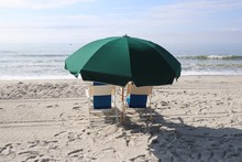 Umbrella And Lounging Chairs On The Beach Facing The Ocean