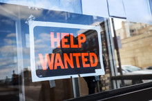 Reflection Of A Man Looking At A Help Wanted Sign In A Business Window, Economy Concept