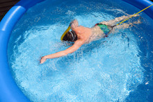 Teen Swimming On A Tether In An Inflatable Pool To Practice During The Pandemic
