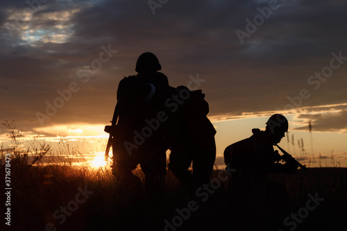 Photo silhouettes of soldiers against the sunset sky
