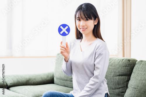Fotografia, Obraz リビングのソファでNGのプラカードを持つ若い女性