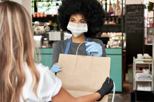 African American Female Cafe Worker Wears Face Mask And Gloves Giving Takeaway Food Bag To Customer. Mixed Race Waitress Holding Takeout Order Standing In Coffee Shop Restaurant With Take Away Client.