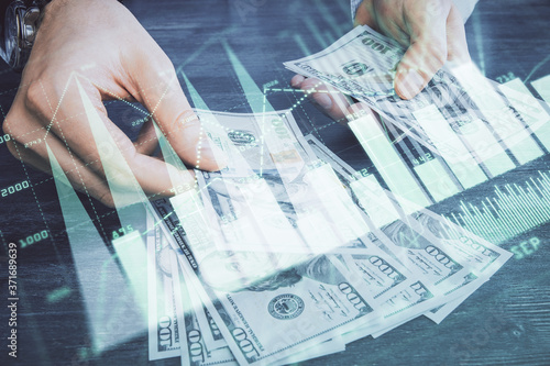 Leinwand Poster Multi exposure of financial graph drawing hologram and USA dollars bills and man hands