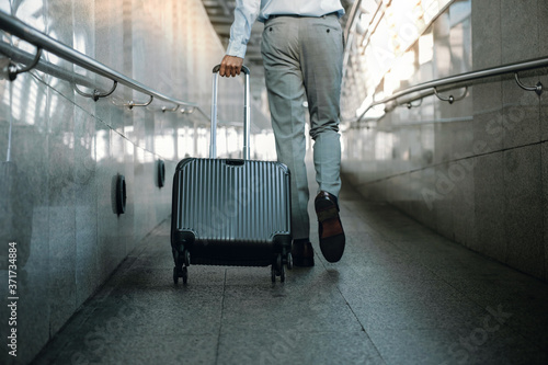 Fotografiet Low Section of Passenger Businessman Walking with Suitcase at the Walkway in Airport