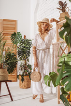 Fashionable Model Wearing Summer White Crochet Jumpsuit, Straw Hat, Sandals, Holding Wicker Bag, Posing At Home, In Stylish Boho Interior With Green Tropical Plants. Full Body Indoor Portrait