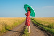 canvas print picture - A young woman in a red dress and a green umbrella is walking along the road along a wheat field. Concept of protection, calmness and freedom