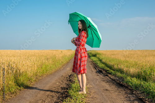 Fényképezés A young woman in a red dress and a green umbrella is walking along the road along a wheat field