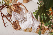 Young Elegant Fashionable Model Wearing Summer White Crochet Jumpsuit, Straw Hat, Heeled Sandals, With Wicker Bag, Sitting On Floor, Posing At Home, In Stylish Boho Interior With Trendy Decorations