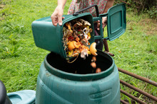 A Woman Emptying A Green Home Composting Bin Into An Outdoor Compost Bin To Reduce Waste