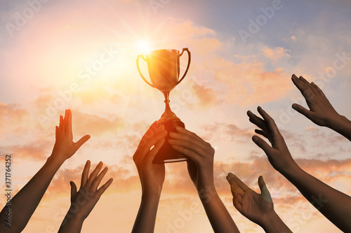 Photo Winning team with gold trophy cup against shining sun in sky
