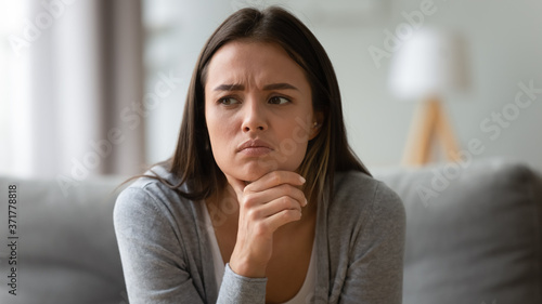 Head shot close up unhappy young brunette frowning woman worrying about difficult decision, sitting on couch indoors Canvas Print