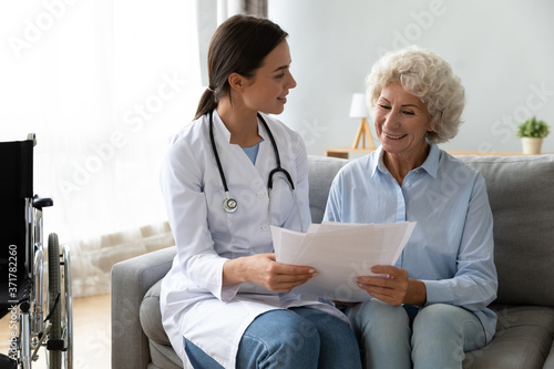 Fototapeta Happy young skilled female general practitioner in white medic uniform visiting disabled smiling middle aged senior patient, showing health analysis on paper, satisfied with treatment results
