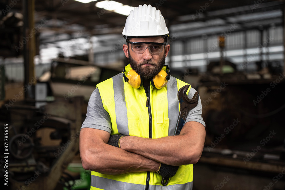 Fototapeta Portrait of technician man or industrial worker with hardhat or helmet, eye protection glasses and vest working electronic machinery on laptop and mechanical  in Factory of manufacturing place