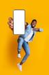 Leinwandbild Motiv Excited african guy dancing with modern smartphone