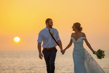Silhouette Of Wedding Couple Walk On Beach In With Sunset Over Gulf Of Mexico