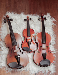 Fototapeta na wymiar Three violins put on background,show detail and different size of acoustic instrument