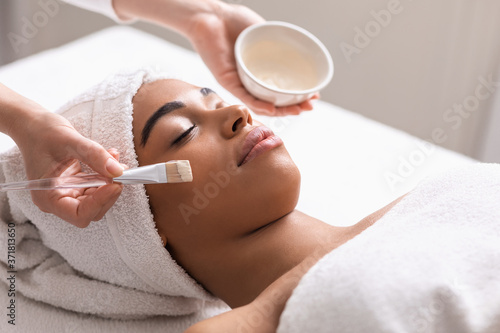 Tableau sur Toile Spa therapist applying face mask for black lady