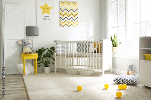 Cute baby room interior with crib and big window