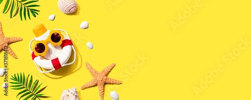 Fotografie, Obraz Sunblock bottle wearing sunglasses with starfish and seashells - flat lay
