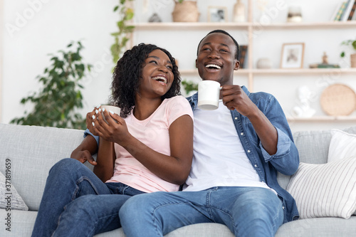 Black couple enjoying weekend together, drinking coffee on couch Fototapete