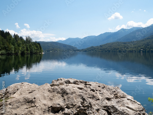 View towards reflecting lake with forest to the left and mountains to the right with rock surface in forefront implying