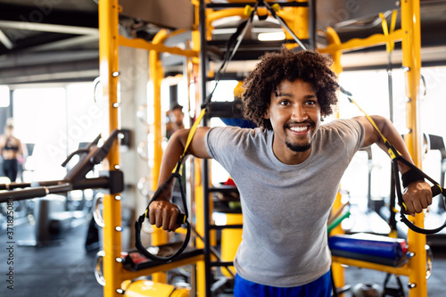 Fotomural Man training with trx fitness straps in the gym