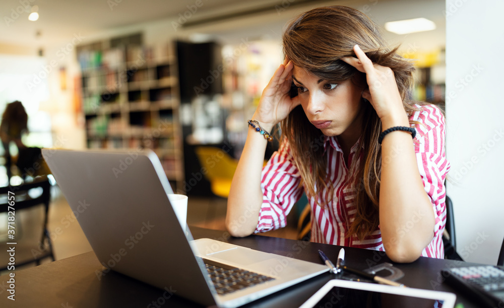 Fototapeta Young depressed tired woman working studying on notebook