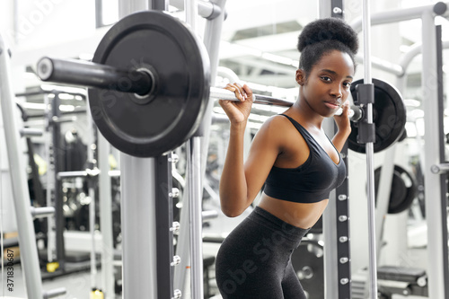 Fotografía athletic african woman pumping up muscles with barbell, crossfit weightlifting o