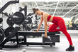 sportive caucasian young woman pumping arm muscles with the use of dumbbells, at modern gym fitness center