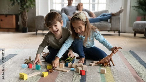 Overjoyed funny little children siblings playing toys on floor carpet while parents resting on sofa. Happy emotional cute little boy having fun with preschool sister, enjoying playtime in living room.