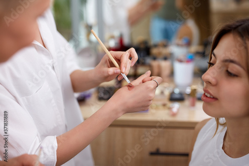 professional make-up artist or visagist apply cosmetics on hand before applying Fotobehang