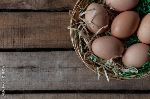 Fotografie, Obraz Eggs in basket on wooden background