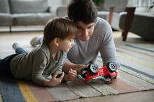 Caring Young Father Lying On Floor Carpet With Little Adorable Kid Son, Teaching Fixing Toy Car In Living Room. Interested Small Child Boy Involved In Repairing Process With Daddy, Skills Development.