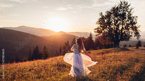 Fotografiet Beautiful bride dancing in blue wedding dress in mountains at sunset