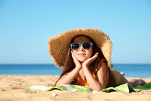 Cute Little Child Lying At Sandy Beach On Sunny Day