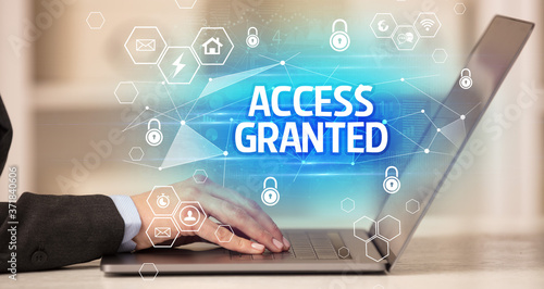 Fototapeta ACCESS GRANTED inscription on laptop, internet security and data protection conc