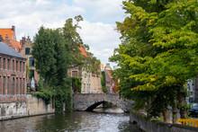 Bridge In Bruges, Belgium, West Flanders (Vlaanderen), Bruges (Brugge). Brugse Vrije And Buildings Along The Groenerei Canal At Dusk.