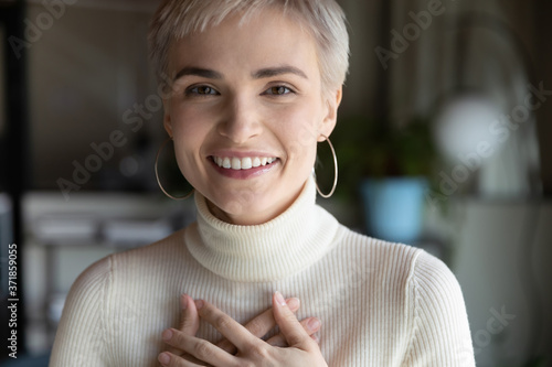 Fotografija Close up head phot profile portrait of kind young businesswoman holding folded hands on chest, feeling thankful