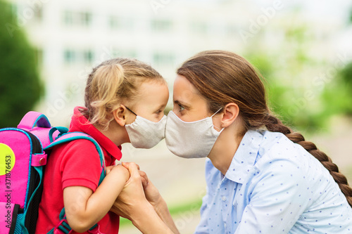 Fotografiet parent and her child look into each other's eyes and both wear protective masks