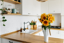 Sunflowers Bouquet In Vase On The Kitchen. View On White Simple Modern Kitchen In Scandinavian Style