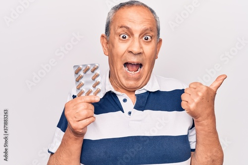 Senior man with grey hair holding pills pointing thumb up to the side smiling ha Fototapeta
