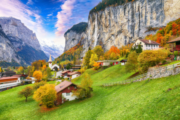 Astonishing autumn view of Lauterbrunnen valley with gorgeous Staubbach waterfall and Swiss Alps in the background.